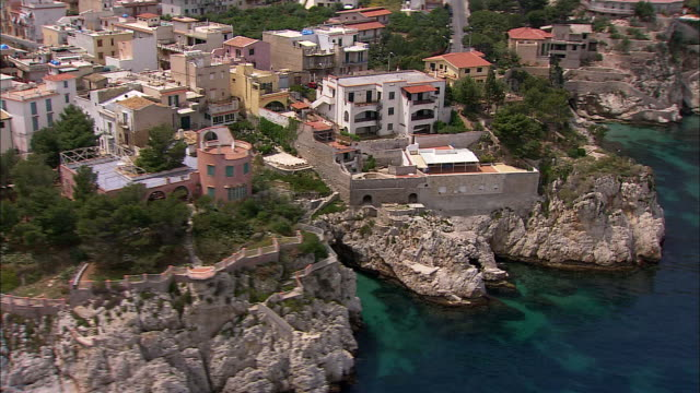 upscale beach houses sit atop stone cliffs rising from the blue waters of the tyrrhenian sea. - mar mediterraneo video stock e b–roll