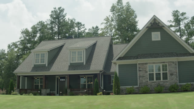 """upscale grey 2 - story house, large yard, trees in back; """"for sale/sold"""" sign in front - sale stock videos & royalty-free footage"""