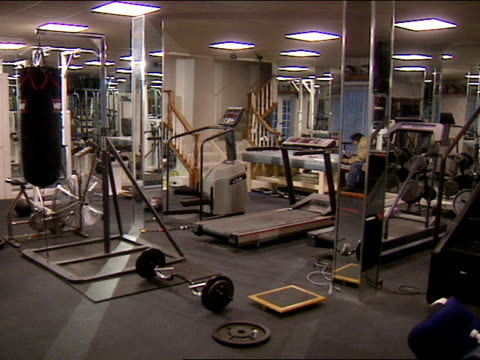 stockvideo's en b-roll-footage met upscale home weight room home gym w/ carpeted stairs leading into room. overhead lighting, mirrored columns, no people. - vrijetijdsfaciliteiten