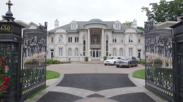 """""""d/x upscale mansion, large open iron gate, crane moves inside, mercedes and rolls royce parked in front"""" - 高級車点の映像素材/bロール"""