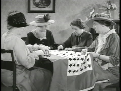 upscale neighborhood. int women sewing stars on flag. sign: 'food will win the war' vs children working in liberty garden. boy in sailor hat holding... - bedclothes stock videos & royalty-free footage