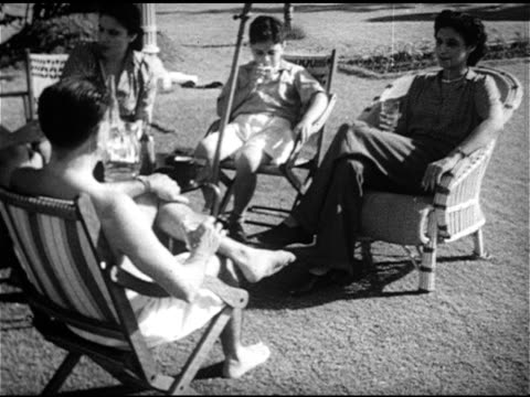 vidéos et rushes de vs upscale parsis family w/ members sitting outside in chairs under umbrella female smoking male drinking beverage zoroastrian community upper class... - 1952