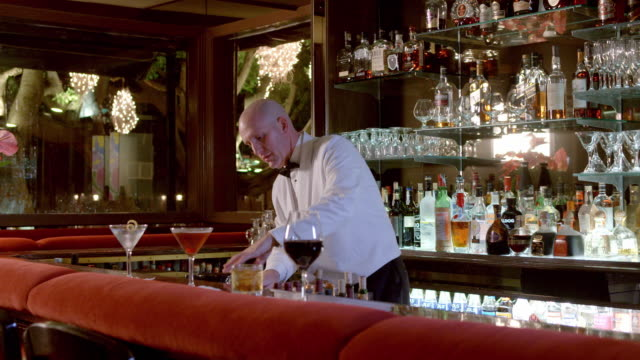 stockvideo's en b-roll-footage met upscale restaurant bar with bartender setting up for customers - martiniglas