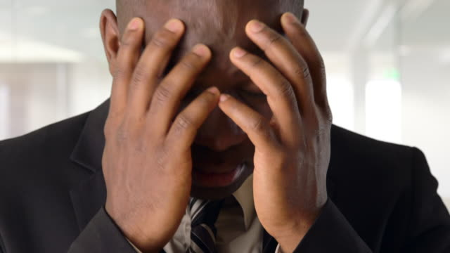 Upset African-American businessman holding head in hands