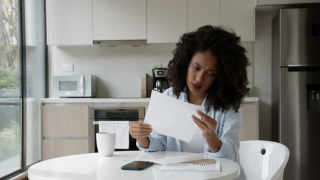 upset black woman checking her correspondence at home - reading mail stock videos & royalty-free footage