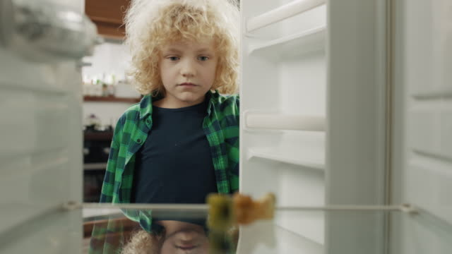 upset boy looking at empty refrigerator - hungry stock videos & royalty-free footage