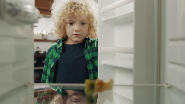 ragazzo sconvolto che guarda il frigorifero vuoto - fame video stock e b–roll