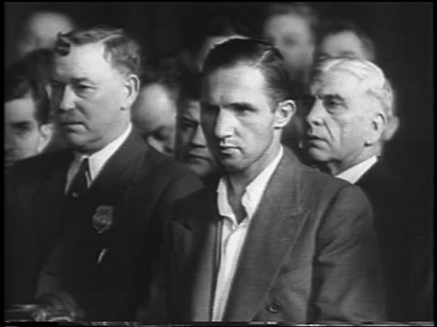 vidéos et rushes de b/w 1935 upset bruno hauptmann standing with lawyers in courtroom / lindbergh kidnapping / newsreel - 1935