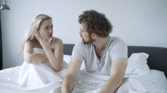Upset couple talking in their bedroom