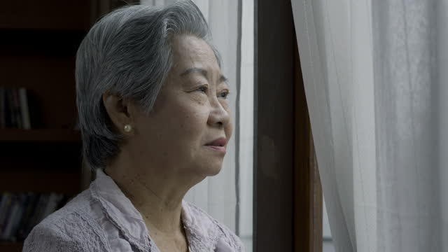 upset elderly lady wiping tears, crying alone near window, loneliness at old age. closeup face of sad old woman with gray hair. - senior women stock videos & royalty-free footage