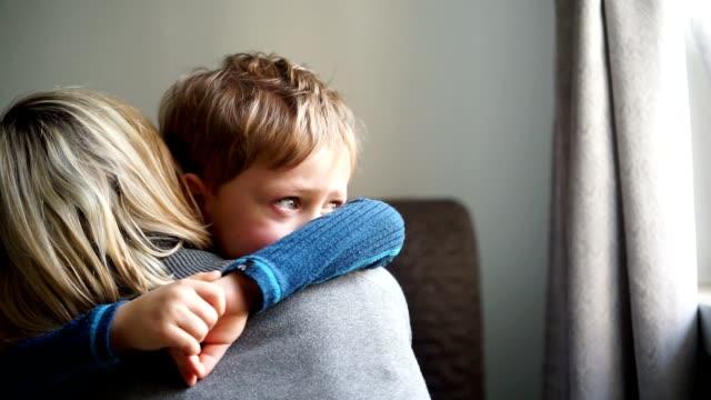 Upprörd liten pojke kramar hans mor hemma