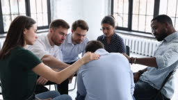 Upset man get psychological support from friends at group therapy