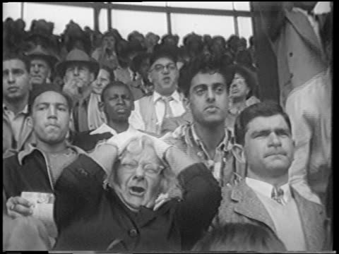 vídeos y material grabado en eventos de stock de b/w 1951 upset senior woman in audience grabbing head making face at playoff game / polo grounds - 1951