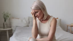 Upset tired old mature woman coping with morning headache concept