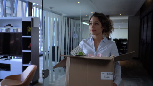 vídeos de stock e filmes b-roll de upset woman carrying a box with her office things after a company downsize - desemprego