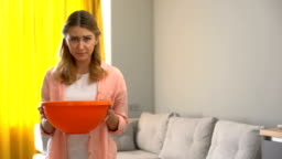 Upset woman holding pot while water leaking from ceiling, house needs renovation
