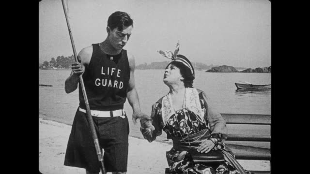 stockvideo's en b-roll-footage met 1917 upset woman on beach pulls lifeguard (buster keaton) aside to ask him a question - 1917