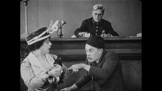 1917 upset woman pays bail for mean man who recoils from picture of man (fatty arbuckle) - releasing stock videos and b-roll footage
