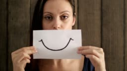 Upset woman showing a smile painted on paper