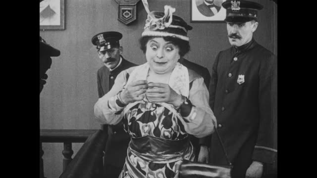 1917 upset woman shows unimpressed police chief a picture of missing man (fatty arbuckle) - report produced segment stock videos & royalty-free footage
