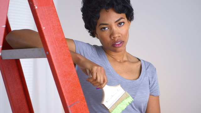 Upset woman with paint brush in hand