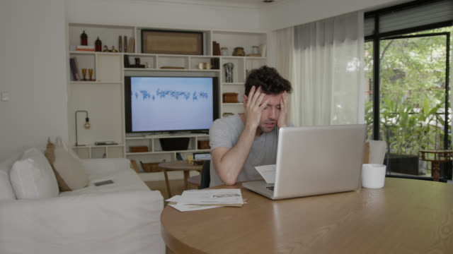 upset young man working from home using a laptop looking at a document and screen - frustration stock videos & royalty-free footage