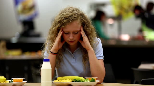 stockvideo's en b-roll-footage met upset young teenager in school cafeteria - kantine