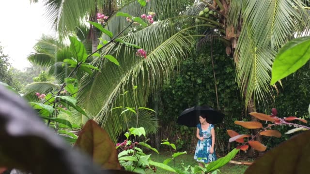 Upset young woman on outdoors vacation holding an umbrella surprised by unexpected tropical rainy day