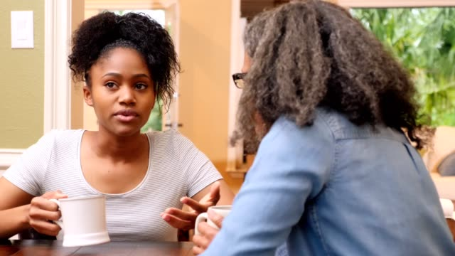 vídeos de stock e filmes b-roll de upset young woman talks with her mom about a difficult situation - consolar