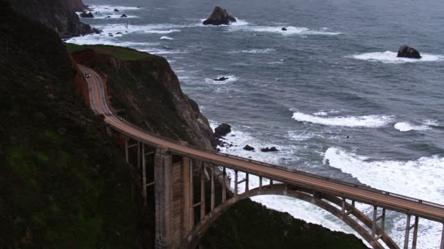 upward tilt from bixby creek bridge to sun set over pacific - aerial - route 001 stock videos & royalty-free footage