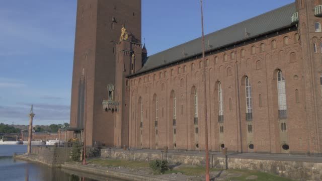 vídeos de stock e filmes b-roll de upward tilt of town hall tower at sunrise, stockholm, sweden, scandinavia, europe - edifício do governo local