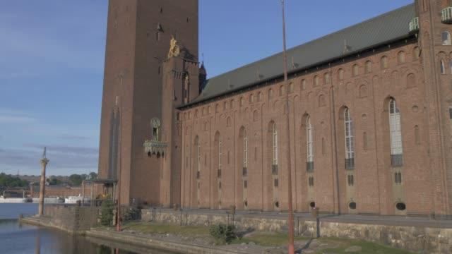 upward tilt of town hall tower at sunrise, stockholm, sweden, scandinavia, europe - rathaus stock-videos und b-roll-filmmaterial