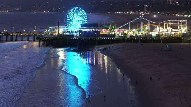 upward tilting aerial of santa monica pier at night - santa monica pier stock videos & royalty-free footage