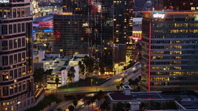 upward tilting drone shot of 110 freeway passing downtown la at dusk - staples center video stock e b–roll