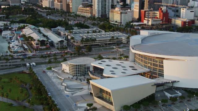 vídeos y material grabado en eventos de stock de upward tilting drone shot of aa arena and downtown miami - bahía de biscayne