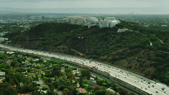 upward tilting drone shot of brentwood revealing sepulveda pass and getty center - brentwood los angeles stock videos & royalty-free footage