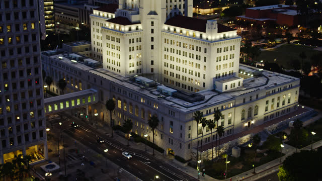upward tilting drone shot of los angeles city hall at twilight - rathaus stock-videos und b-roll-filmmaterial