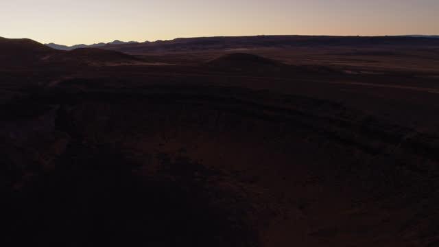upward tilting drone shot of lunar crater national natural landmark at nightfall - natural landmark stock videos & royalty-free footage