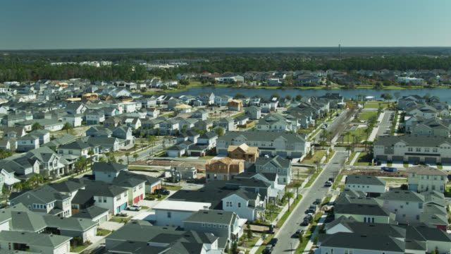 upward tilting drone shot of new suburban homes near orlando - tract housing stock videos & royalty-free footage