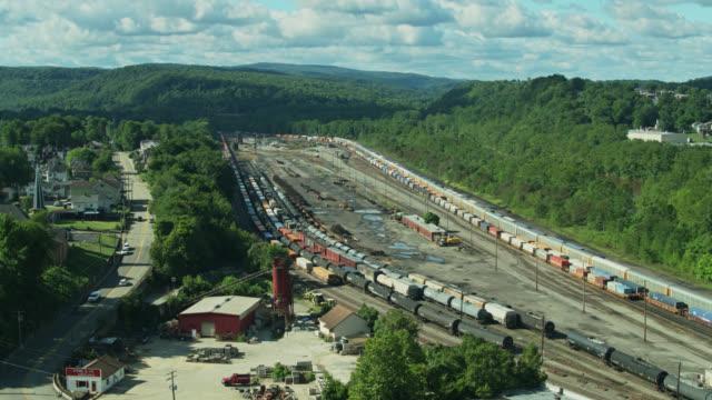 stockvideo's en b-roll-footage met upward tilting drone shot of rail yard in pennsylvania - straatnaambord