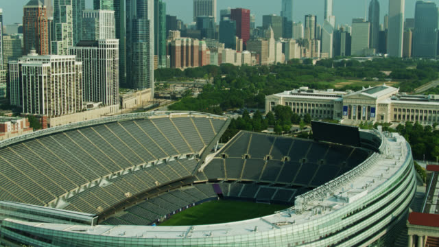 upward tilting drone shot of soldier field with reveal of chicago landmarks - chicago illinois stock videos & royalty-free footage