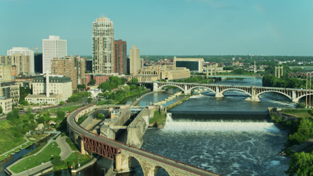 upward tilting drone shot of the mississippi flowing beneath bridges and over waterfalls in minneapolis - minnesota stock videos & royalty-free footage