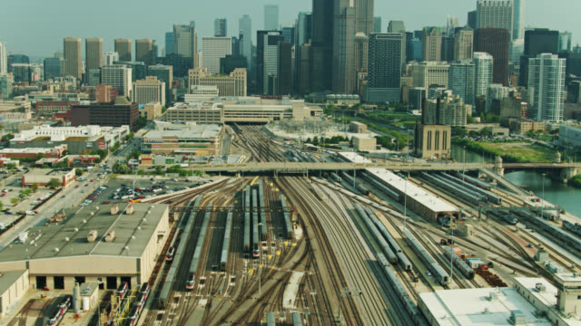 upward tilting drone shot of train yard and downtown chicago skyline - willis tower stock videos & royalty-free footage