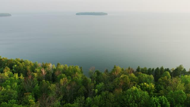 vidéos et rushes de upward tilting drone shot revealing horseshoe island in lake michigan's green bay from peninsula park, wisconsin - cîme d'un arbre