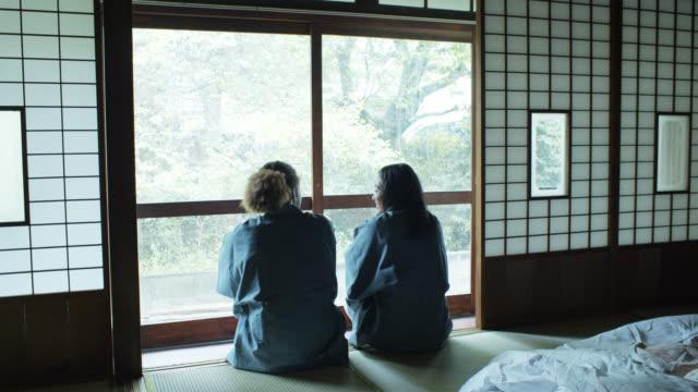 stockvideo's en b-roll-footage met opwaartse kantelen shot van paar in yukata op zoek uit raam in ryokan - ryokan