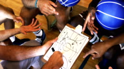 Upward view of coach assisting players on clipboard clipboard