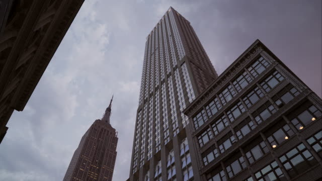 Upward view of Empire State Building and neighboring skyscraper