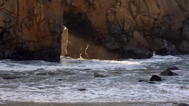 vídeos de stock e filmes b-roll de upwards pan to sun shaft and waves through opening of keyhole arch, pfeiffer beach, central big sur coast, monterey county, california, 4k video - arco natural