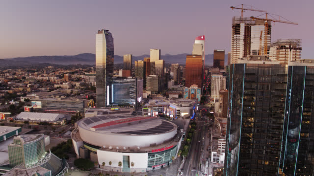 vídeos de stock e filmes b-roll de upwards tilting drone shot from staples center towards dtla financial district at sunset - microsoft theater los angeles