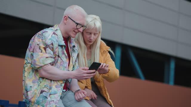 urbane und moderne albino-freunde, die gemeinsam spaß haben, während sie interessante inhalte im internet ansehen - content stock-videos und b-roll-filmmaterial